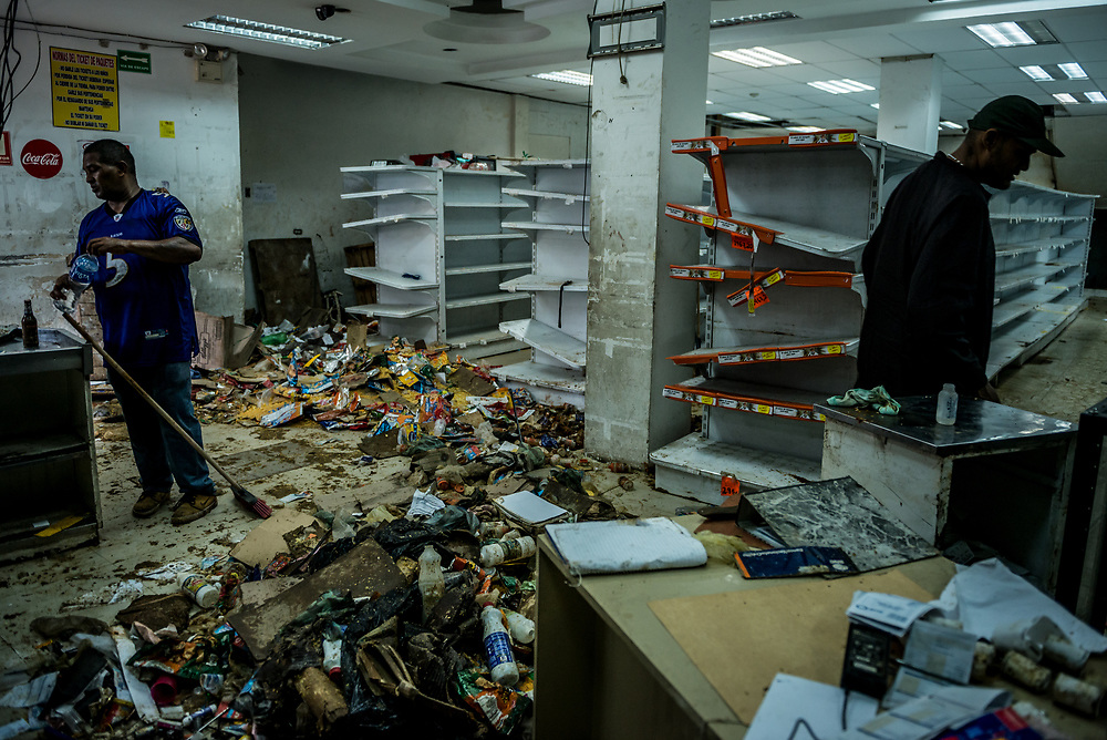 CARACAS, VENEZUELA - APRIL 21, 2017:  Gregorio Rodríguez (left) and José Prada (right) work to clean the Ofercenter supermarket where they work, and that was one of over a dozen stores looted late last night in El Valle, a working class neighborhood in Caracas. The streets of Caracas erupted into a night of riots, looting and clashes with National Guardsmen as anger from two days of pro-democracy protests spilled into unrest in working class neighborhoods and slums. Shots rang out throughout the night in El Valle, a neighborhood of mixed loyalties, as armored vehicles struggled to contain crowds of looters. At one point during the night, clashes became so heavy that a nearby children's hospital was evacuated after the ward filled with tear gas. The government said they were responding to an attack on the hospital by opposition protestors.  PHOTO: Meridith Kohut