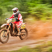 Panning shot shows mud splattering and brown water puddles splashing from dirt trail as motocross racer competes during extreme sporting event in Belmopan, Belize.