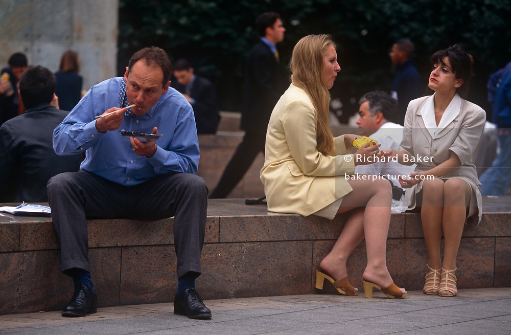 Nineties office workers in the Square Mile - the capital's financial district - eat lunch outside, on 21st June 1997, in Broadgate, London, England.