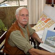 Dhr Behring met papieren en bezwaren ivm dakopbouwen Stad en Lande Huizen