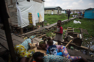 Abiodun Ibrahim, 24, left, rests with friends and their kids in a makeshift living area several days after a fire destroyed her rented room and all of her possessions in the Badia neighborhood of Lagos, Nigeria, August 21, 2013.  Abiodun who is unemployed and three months pregnant by her common law husband-- currently serving time in prison-- is considering an abortion.  As the primary caretaker for her three-year-old nephew, she barely makes ends meet and says she doesn't know how she will be able to provide for another child.