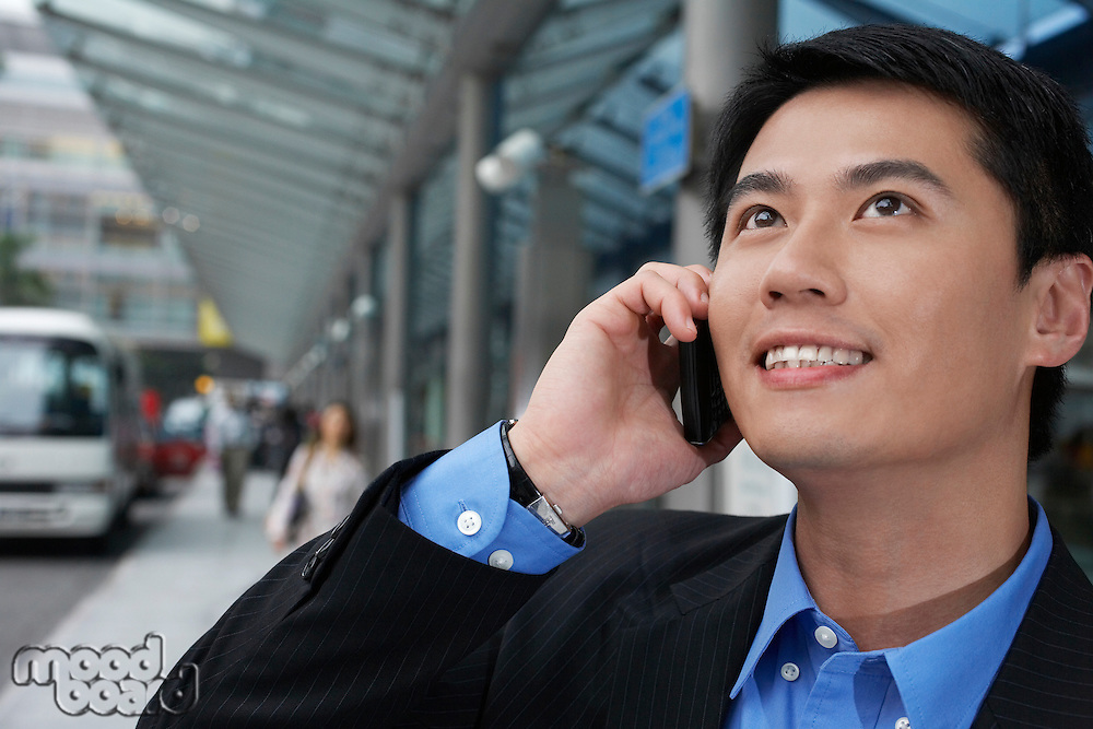 Business man using mobile phone on street close up
