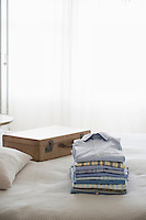 Ironed and folded shirts next to a suitcase