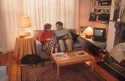 Couple sitting on sofa in living room reading,