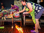 """05 SEPTEMBER 2017 - BANGKOK, THAILAND:  A woman lights incense after setting up her family's Hungry Ghost banquet in Chinatown in Bangkok. The Ghost Festival is a Buddhist and Taoist holy day celebrated on the 15th day of the 7th lunar month. It is primarily celebrated in China and Chinese communities outisde China. In Thailand, it's celebrated in Thai-Chinese communities in Bangkok, Phuket and Chiang Mai.  On that day ghosts and spirits, including those of the deceased ancestors, come out from the lower realm to visit the living. Families prepare elaborate banquets for the spirits and burn """"ghost money"""" for the spirits to use in the other realm. It is a day for venerating dead relatives.     PHOTO BY JACK KURTZ"""