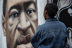 "© Licensed to London News Pictures . 22/07/2020 . Manchester , UK . A woman watches as a mural to George Floyd in the Northern Quarter of Manchester City Centre is repainted by the artist after it was sprayed with racist graffiti . "" Nigger "" was sprayed across the face of the artwork by Manchester artist AKSE overnight . Photo credit : Joel Goodman/LNP"