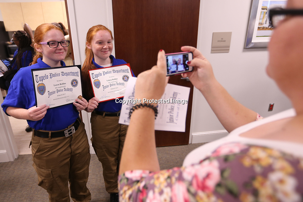 Laren and Laken Rollins, from Fulton, hold up their graduation certificates as their mother, Amber Mackey, takes a photo. The two completed the two week Junior Police Academy with the Tupelo Police Department with 20 other cadets with the commencement ceremony being held in the community room at the Tupeo Police Department Friday morning.