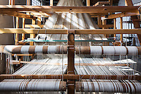 """SOVERIA MANNELLI, ITALY - 17 NOVEMBER 2016: A Jacquard loom (a power loom that simplifies  the process of making textiles) is seen here at the Lanificio Leo woolen mill in Soveria Mannelli, Italy, on November 17th 2016.<br /> <br /> Lanificio Leo was the first and last machine-operated woolen mill of Calabria, founded in 1873, it employed 50 people until the 1970s, when national policies to develop Italy's South cut out small businesses and encouraged larger productions or employment in the public administration.<br /> <br /> The woolen mill was on stand-by for about two decades, until Emilio Salvatore Leo, 41, started inviting international designers and artists to summer residencies in Soveria Mannelli. With their inspiration, he tried to envision a future for his mill and his town that was not of a museum of the past,<br /> Over the years, Mr. Leo transformed his family's industrial converter of Calabrian wool into a brand that makes design products for home and wear. His century old machines now weave wool from Australia or New Zealand, cashmere from Nepal and cotton from Egypt or South America. He calls it a """"start-up on scrap metals,"""" referring to the dozens of different looms that his family acquired over the years.<br /> <br /> Soveria Mannelli is a mountain-top village in the southern region of Calabria that counts 3,070 inhabitants. The town was a strategic outpost until the 1970s, when the main artery road from Naples area to Italy's south-western tip, Reggio Calabria went through the town. But once the government started building a motorway miles away, it was cut out from the fastest communications and from the most ambitious plans to develop Italy's South. Instead of despairing, residents benefited of the geographical disadvantage to keep away the mafia infiltrations, and started creating solid businesses thanks to its administrative stability, its forward-thinking mayors and a vibrant entrepreneurship numbering a national, medium-sized publishing house"""