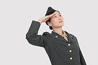 Serious female US military officer saluting over gray background
