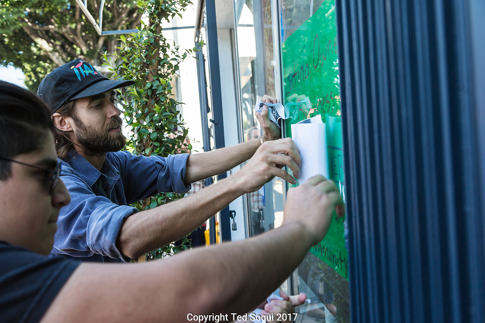 Owners of the coffee shop remove stickers from their window.<br /> Boycott and demonstration against Weird Wave Coffee House on Caesar E. Chavez Ave in Boyle Heights. About 25 demonstrators held signs and chanted slogans out front of the coffee house.