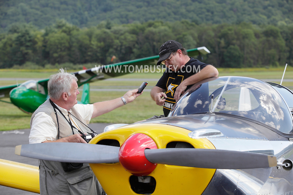 Wurtsboro, NY - A journalist interviews a pilot by his plane during a fly-in at Wurtsboro Airport on Aug. 30, 2009.