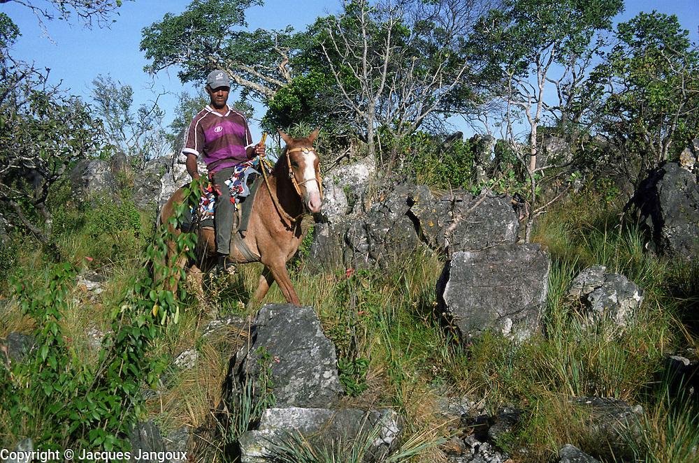 """Small farmer riding hose in """"campos rupestres"""", rock outcrop in savanna (cerrado)."""