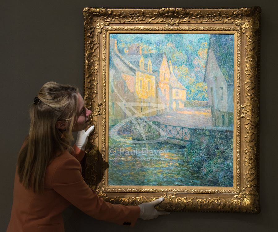 Bonhams, London, February 27th 2017. A member of Bonham's staff straightens Henri Le Sidaner's 'Matin doré', which is expected to fetch between £150,000 and £200,000, at the Bonhams impressionist and modern art sale press preview at their Mayfair gallery in London.