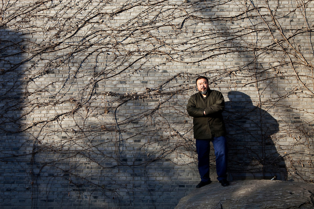 "Ai Weiwei, (born 1957, Beijing) in his courtyard at his studio. He is a leading Chinese artist, curator, architectural designer, cultural and social commentator and activist. Ai is known for the design of the Beijing National Stadium, more commonly known as the ""Bird's Nest"", the main stadium of the 2008 Olympic Games in Beijing. Beginning with the 2008 Sichuan earthquake, Ai has emerged as one of China's most influential bloggers and social activists; he is known for his tongue-in-cheek and sometimes vulgar social commentary, and has had frequent run-ins with Chinese authorities. He was particularly focused at exposing an alleged corruption scandal in the construction of Sichuan schools that collapsed during the earthquake.Born in Beijing, his father was Chinese poet Ai Qing, who was denounced during the Cultural Revolution and sent off to a labor camp in Xinjiang with his wife, Gao Ying. Ai Weiwei also spent five years there. Ai Weiwei is married to artist Lu Qing. Ai Weiwei is represented by Galerie Urs Meile Beijing-Lucerne. Beijing, China. 2010"