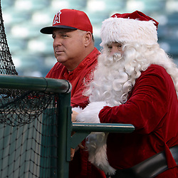 Los Angeles Angels manager Mike Scioscia, left, with Los Angeles Angels chairman Dennis Kuhl as Santa Claus prior to a baseball game against Minnesota Twins at Anaheim Stadium in Anaheim, Calif., on Wednesday, June 25, 2014.