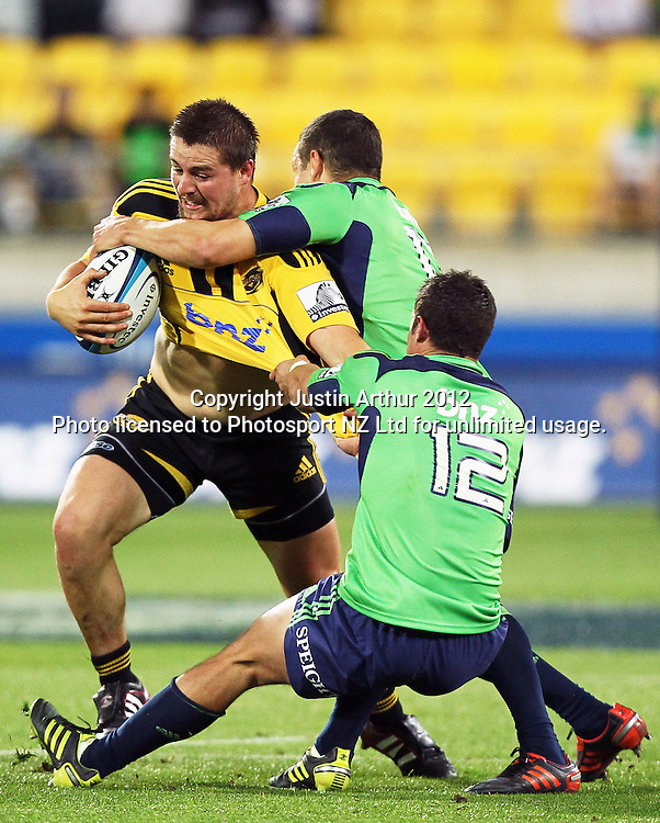 Hurricanes' Dane Coles is wrapped up by Highlanders' Phil Burleigh and Tamati Ellison during the 2012 Super Rugby season, Hurricanes v Highlanders at Westpac Stadium, Wellington, New Zealand on Saturday 17 March 2012. Photo: Justin Arthur / Photosport.co.nz