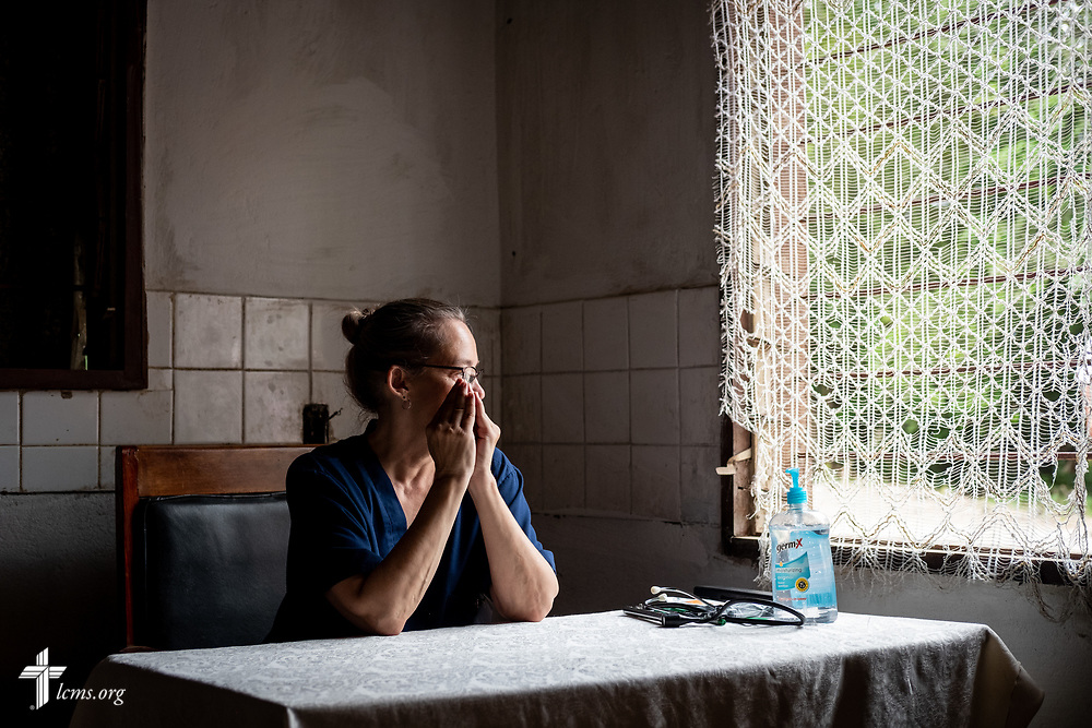 Nurse Donna Mulholland, a member of Shepherd of the Valley Lutheran Church, Fort Bridger, Wyo., pauses for a moment before the door opened on the third day of the LCMS Mercy Medical Team on Wednesday, May 9, 2018, in the Yardu village outside Koidu, Sierra Leone, West Africa. LCMS Communications/Erik M. Lunsford