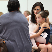 Alice Fagan, 7, enjoys a seat in her mother's lap as they wait on her sister to finish her audition for the Nutcracker on Sunday.