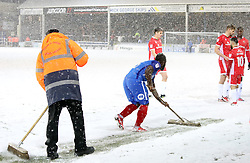 Junior Morias of Peterborough United clears snow off the pitch during the match after heavy snow covers the pitch - Mandatory by-line: Joe Dent/JMP - 27/02/2018 - FOOTBALL - ABAX Stadium - Peterborough, England - Peterborough United v Walsall - Sky Bet League One