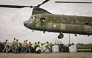 National guard units from Maryland and Pennsylvania work with workers from the  Hard Rock Construction company to load 5000 pound sandbags onto helicopters. The bags are being dropped into a 300-foot-long breech in a levee south of Myrtle Grove in Plaquemines Parish caused by Hurricane Gustav.