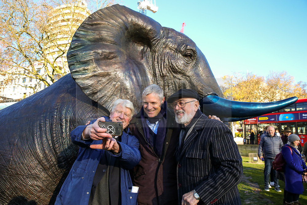 © Licensed to London News Pictures. 04/12/2019. London, UK. Author and father of the Prime Minister BORIS JOHNSON, STANLEY JOHNSON, Parliamentary Conservative candidate for Richmond Park and North Kingston and former Tory candidate for Mayor of London ZAC GOLDSMITH and Actor PETER EGAN take a selfie during the unveiling of life-sized herd of 21 bronze elephants at Marble Arch.<br /> Children unveil a herd of 21 bronze elephants at Marble Arch. The sculpture is the largest such depiction of an elephant herd in the world and is intended to draw attention to the plight of this species that could be extinct on current trends, by 2040. Each elephant in the sculpture is modelled after a real orphaned animal currently in the care of the Sheldrick Wildlife Trust. Left behind by poachers and other sources of human-wildlife conflict these animals have been raised by the trust in an effort to secure the future of the species. The herd will be displayed until 4 December 2020. Photo credit: Dinendra Haria/LNP