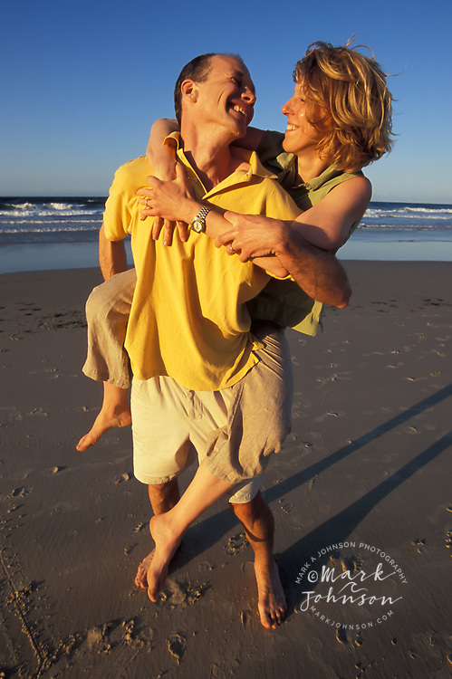 Happy couple playing around on the beach, Queensland, N. Stradbroke Island, Australia