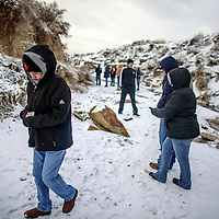Guests walk through the arroyo adjacent to the Crystal Carwash before a candlelight vigil for Derek Smith in Gallup Monday.  Smith was found Jan. 27. in the arroyo.