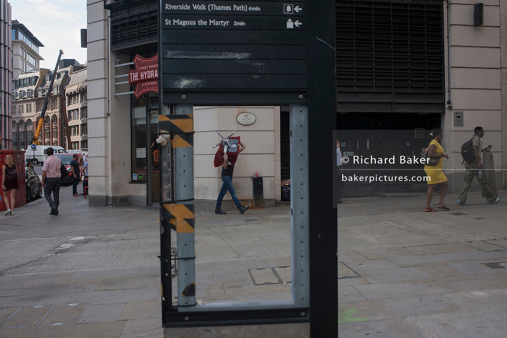 A man carrying an old office chair, seen through a missing map panel, on 13th September 2016, in the City of London, England.