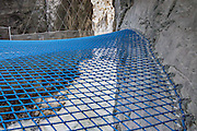 Walk across a blue net suspended over the White Lütschine river gorge, in the Gletscherschlucht of Grindelwald, Switzerland, Europe. Walk boardwalks and tunnels through the dramatic Gletscherschlucht, a deep gorge of the White Lütschine river, flowing from Lower Grindelwald Glacier. From Gletscherschlucht hotel restaurant in Grindelwald, a wooden walkway leads over raging water, through galleries and rocky tunnels over 1000 meters into the ravine, under 100-meter high cliffs. Visitors can amble on a blue net over the foaming torrent. Walk there in 35 minutes from the center of Grindelwald, or take the bus. The tongue of Lower Grindelwald Glacier last extended through Gletscherschlucht gorge in 1855 and has receded very rapidly, melting back more than 3.75 kilometers as of 2014. Consistent with a pattern global warming, the glacier may entirely disappear by 2100.