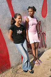 Two girls leaning against a wall in the park,