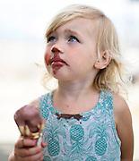 A young girl eats a chocolate ice cream cone.
