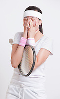 Young female tennis player with hands on face against white background