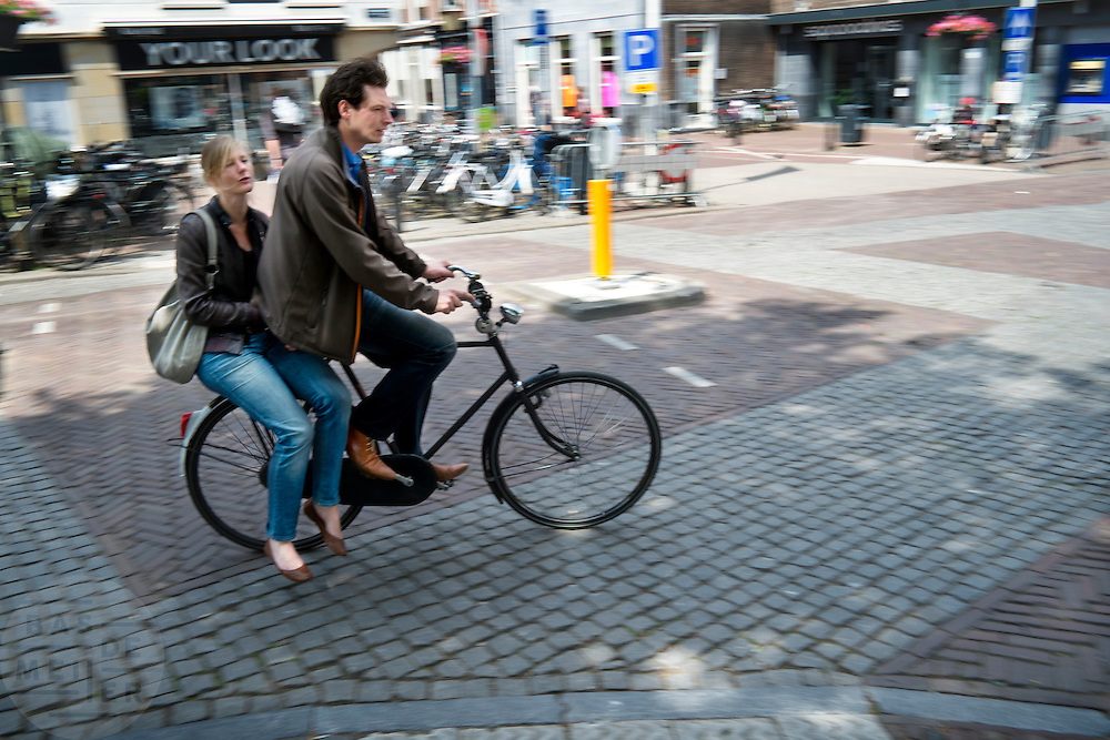 Een man fietst met een vrouw achter op de fiets door Utrecht.<br />