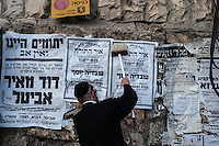 A man plasters posters on a wall in the Mea Sharim neighborhood of Jerusalem