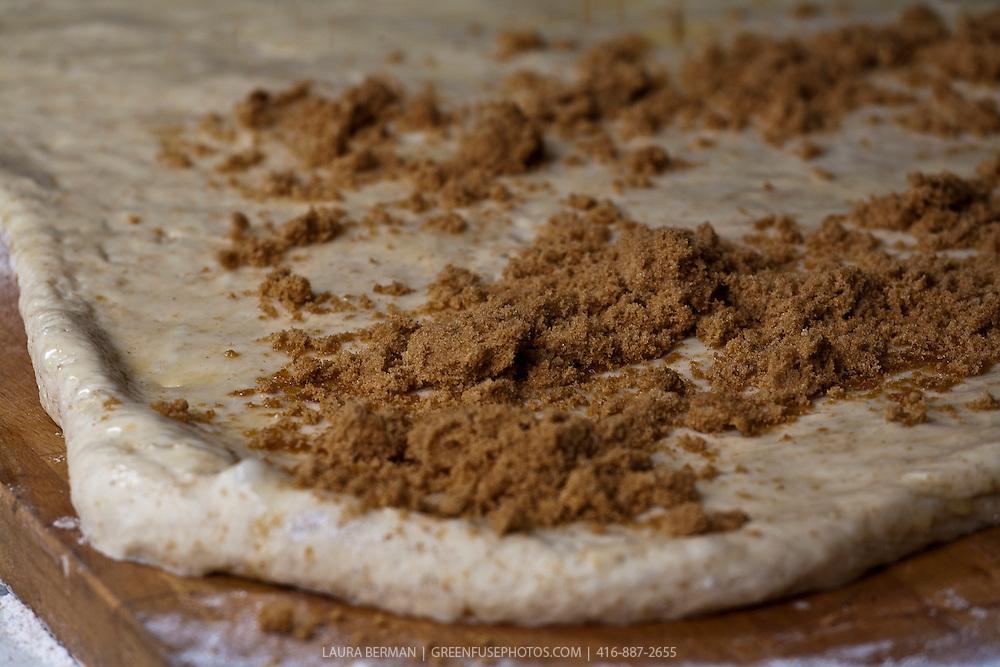 Sugar and cinnamon on dough for cinnamon buns