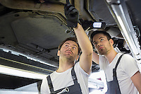 Male mechanics examining car in workshop