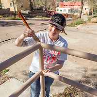 Skills USA participant Aurelia Jones paints the corner of a railing at the Battered Families Services center in Gallup Sunday.