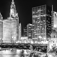 Chicago River cityscape panorama photo with Wabash Avenue Bridge at night in black and white. Panorama photo ratio is 1:3 and includes Hancock Building, Trump Tower, Wrigley Building, and Equitable Building.