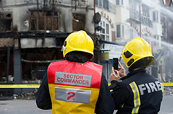 © Licensed to London News Pictures. 09/08/2011. London, UK. A firewoman takes a video on her mobile phone of the wreckage she has dealt with following last night's riots on the corner of St. James Street and London Road, Croydon. Photo credit : Mary Stamm-Clarke/LNP