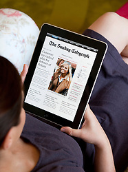 woman reading The Sunday Telegraph newspaper online edition on an iPad tablet computer