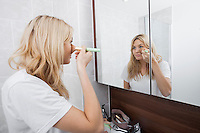 Young woman applying blush while looking at mirror in bathroom