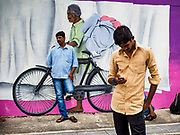 "09 JULY 2017 - SINGAPORE: Guest workers from the Indian sub-continent in front of a mural in Singapore. There are hundreds of thousands of guest workers from the Indian sub-continent in Singapore. Most work 5 ½ to six days per week. On Sundays, the normal day off, they come into Singapore's ""Little India"" neighborhood to eat, drink, send money home, go to doctors and dentists and socialize. Most of the workers live in dormitory style housing far from central Singapore and Sunday is the only day they have away from their job sites. Most work in blue collar fields, like construction or as laborers.    PHOTO BY JACK KURTZ"