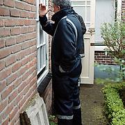 Brand Schipperstraat 22 Huizen, brandweerman kijkt door de ramen