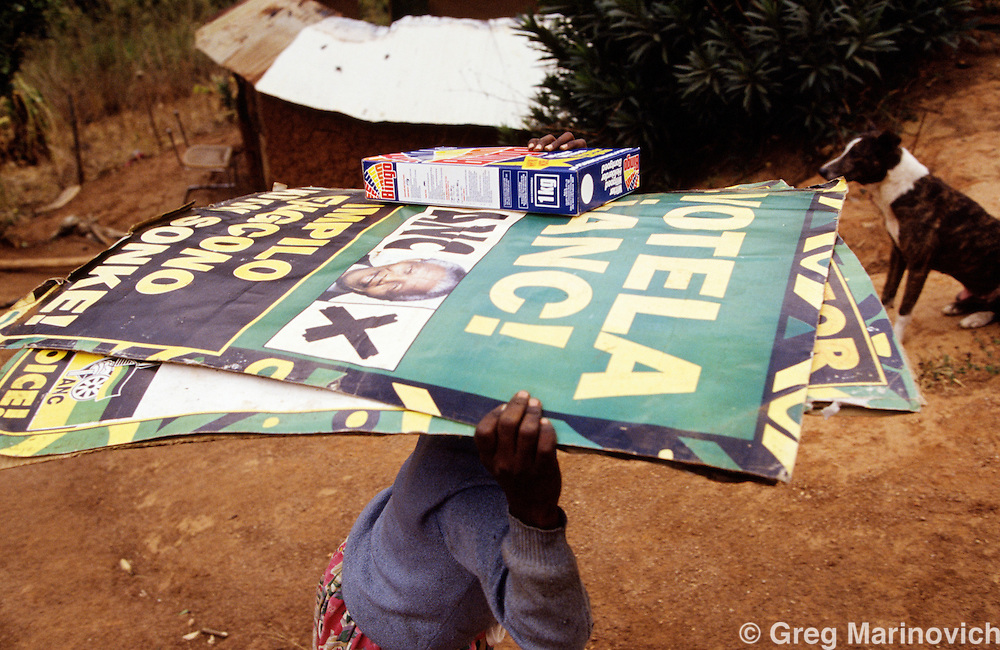 Sonkombo, KwaZulu Natal, 1994, South Africa: A young girl carries  ANC posters as ANC supporting families make their way back to the Sonkombo area from which they had fled months earlier because of attacks by rival IFP.