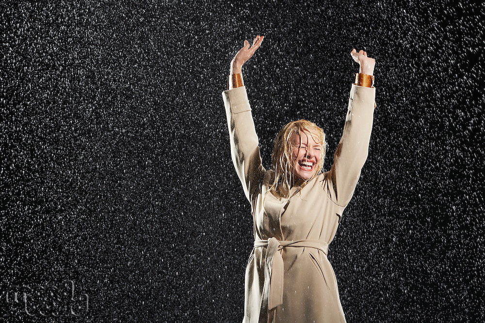 Woman arms outstretched smiling standing in rain