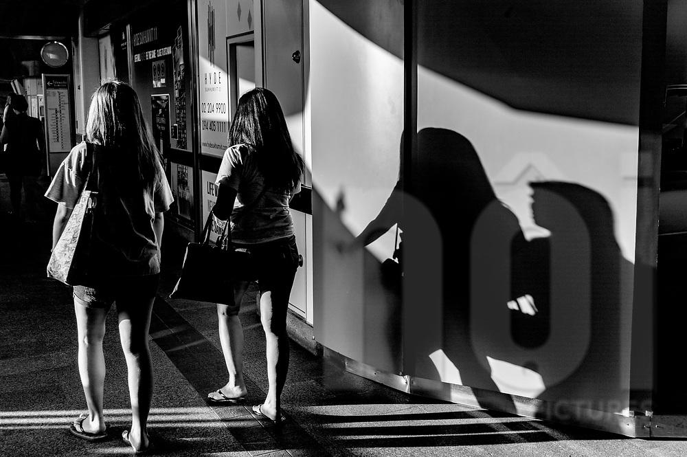 Silhouettes of two women walking through the Nana BTS Station, Bangkok, Thailand, Southeast Asia