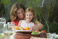Mother and daughter (5-6) sitting at garden table smiling