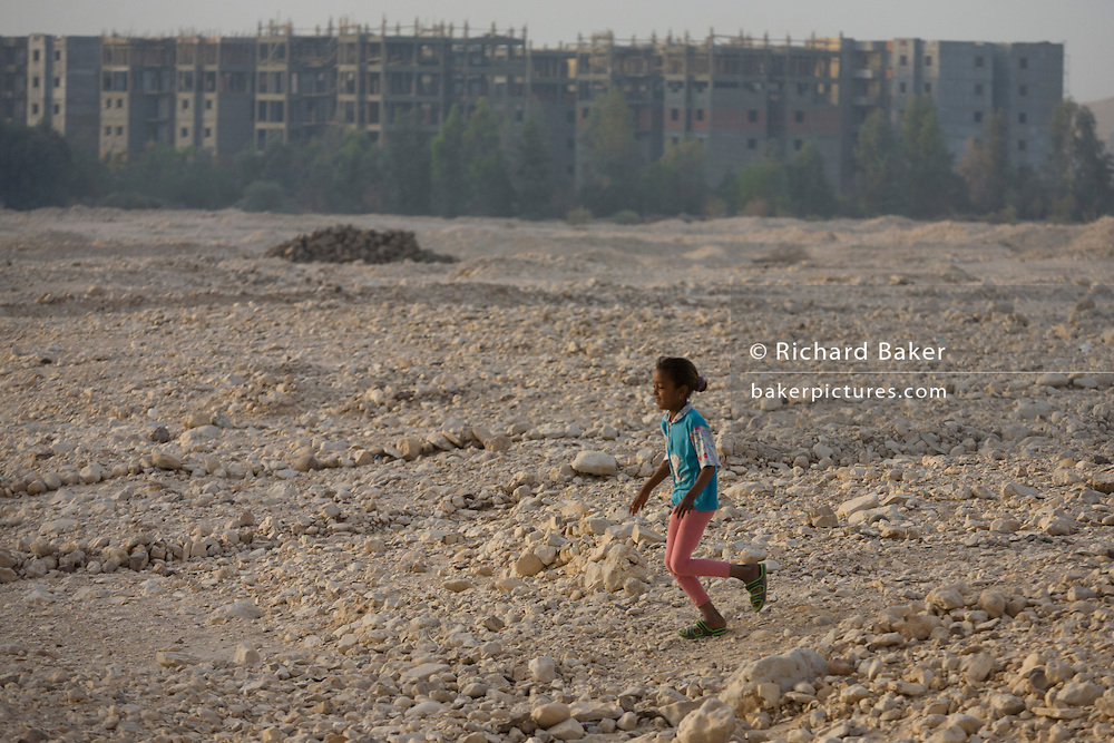 A young Egyptian girl runs over wasteground in front of  local housing in a West Bank village of the modern city of Luxor, Nile Valley, Egypt.