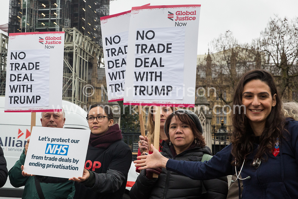 London, UK. 25 November, 2019. A NHS doctor from Oxford (r) addresses campaigners from Keep Our NHS Public, Health Campaigns Together, We Own It and Global Justice Now at a protest in Parliament Square to call on Prime Minister Boris Johnson to end privatisation of healthcare in the National Health Service (NHS).