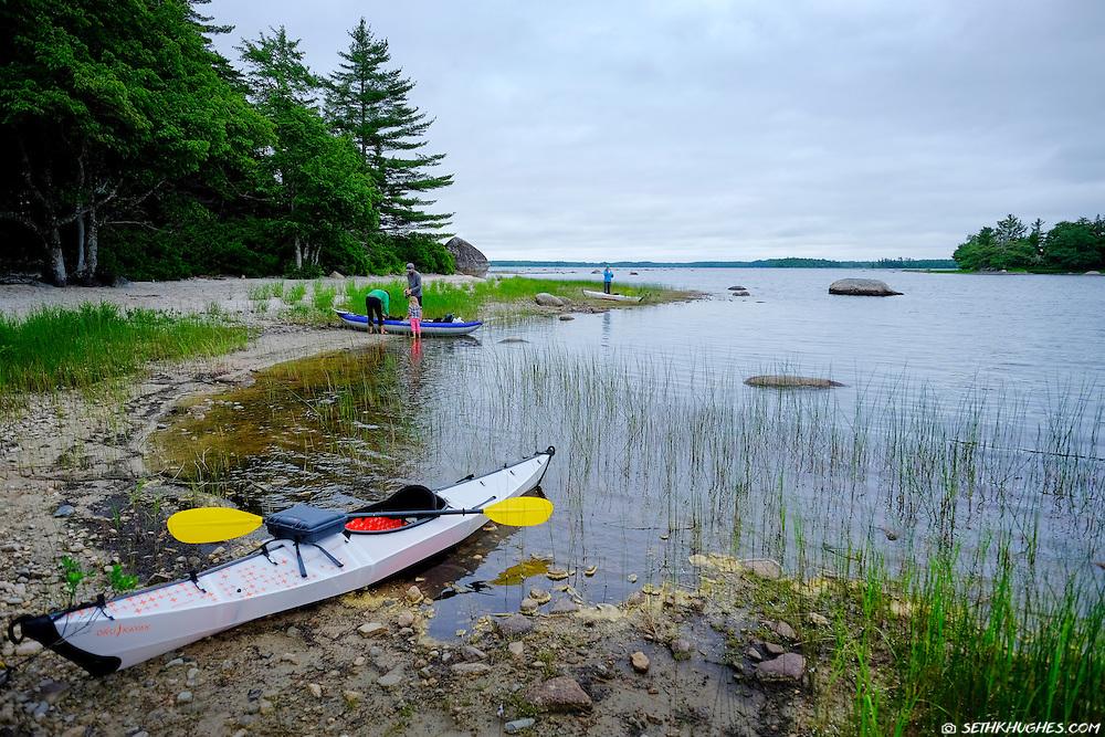 A group of kayakers on the beach in Kejimkujik National Park, Nova Scotia, CA
